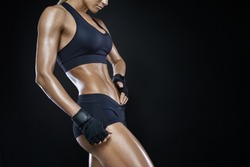 Athletic woman with strong abdominal muscles posing with her hands on her hips with copy space. Attractive muscular woman with gloved hands on strong abs. Muscular pumped woman after workout.