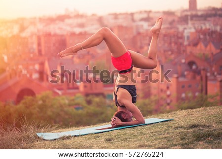 athletic woman working out on a mat in the park, doing handstands against a blurred background of a city at sunset