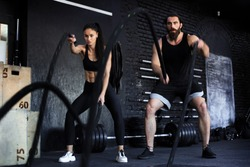 Athletic young indian couple with battle rope doing exercise in functional training fitness gym.