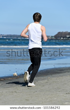 Athletic young male running on the beach. From the back