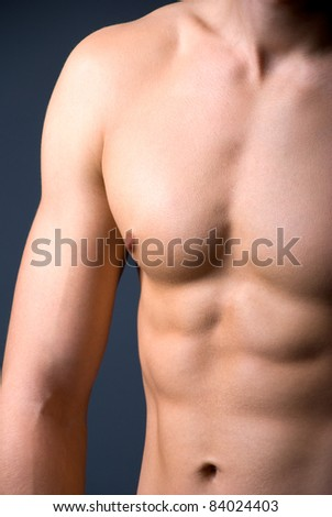 Athletic young male's torso. Dark background, studio shot