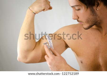 Athletic young man measuring biceps with tape meter