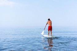 Athletic young man paddling on a sup board on the quiet sea - Stand up paddle boarder training on a rowing board on a flat calm sea - Back view and copy space for text