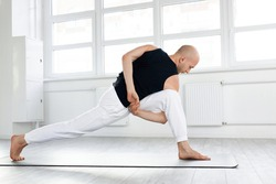 Athletic young man performing complex exercises and keeps balance. Professional yogi guy doing yoga in gym or studio, indoors. bald guy having athletic physique. side view