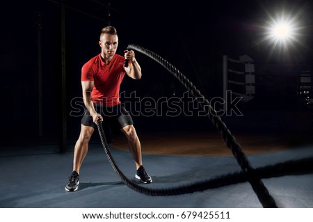 Athletic young man with battle rope doing exercise in functional training fitness gym