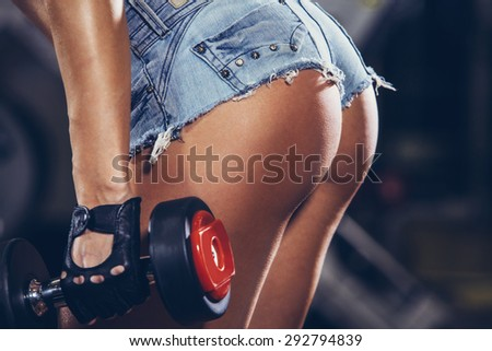 Athletic young woman doing a fitness workout with weights. buttocks close-up.
