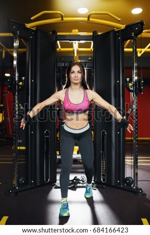 Shutterstock Athletic young woman doing exercise on the chest in the crossover in the gym