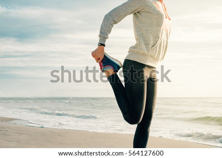 Athletic young woman doing sport exercises on the beach in the morning. The concept of a healthy lifestyle. #564127600