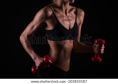 Athletic young woman doing workout with weights on dark background