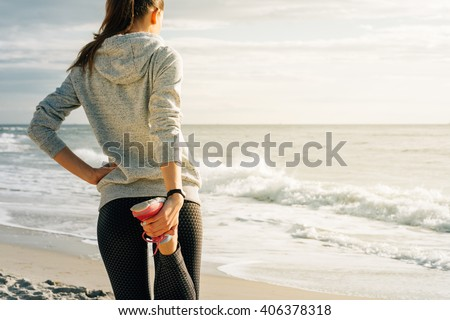 Athletic young woman engaged in morning exercises on the beach during sunrise, view from the back. The concept of a Healthy lifestyle.