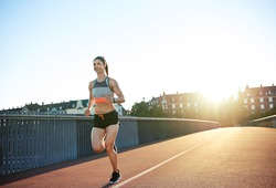 Athletic young woman enjoying a morning run crossing an urban bridge backlit by a bright sunrising above the townhouses in an active lifestyle concept