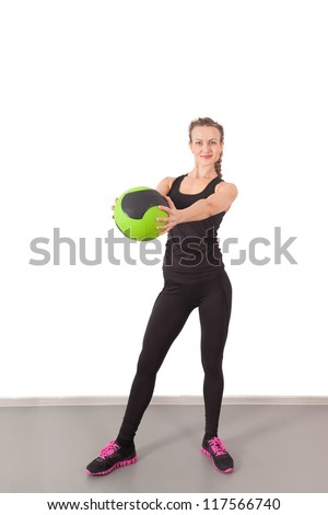 Athletic young woman training with green ball in the gym