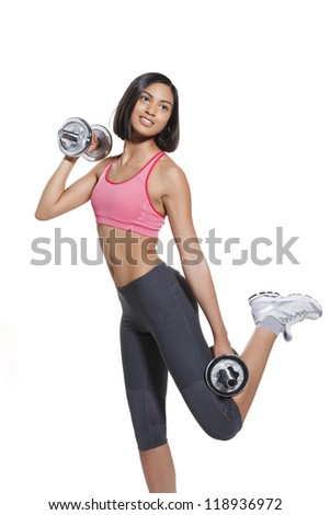 athletic young woman with barbells during workout. on white background