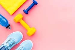 Athletics accessories. Dumbbells, towel, sneakers on pink background top-down copy space