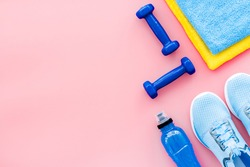 Athletics background with dumbbells, towel, sneakers on pink background top view copy space