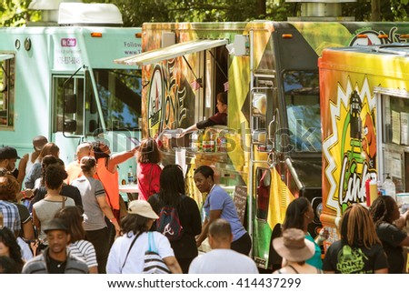 ATLANTA, GA - APRIL 16: A crowd of people buy meals from food trucks lined up in Grant Park at the Food-o-rama festival on April 16, 2016 in Atlanta, GA.