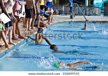 ATLANTA, GA - JUNE 28 : Unidentified young swimmers during the Lake Forest Lightening vs. St. Marlo swim meet relay competition on  June 28, 2012, Lake Forest was the winner. - stock photo