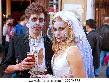 ATLANTA, GA - OCTOBER 20:  An unidentified couple dressed like a zombie bride and groom, enjoy a cold beer after walking in the Little Five Points Halloween parade on October 20, 2012 in Atlanta.