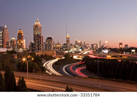 Atlanta skyline just before sunset showing downtown buildings, roads and traffic streaks.