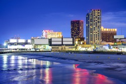 Atlantic City, New Jersey, USA resort casinos cityscape on the shore at night.
