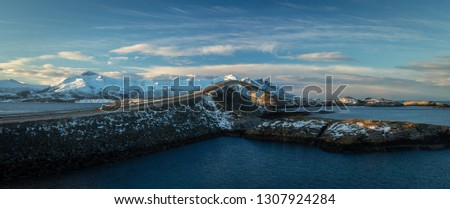 Atlantic Ocean Road - Atlanterhavsvegen in winter sunny day. Famous high bridge over the sea called Storseisundbrua and beautiful snowy mountains in a horizon.