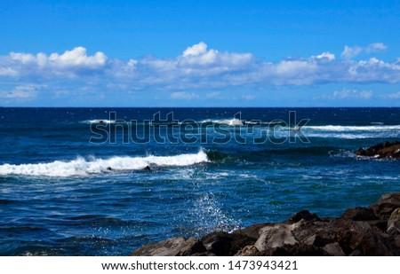 Atlantic Ocean seascape.Waves splashing on rocky coast and blue sky with clouds.Tenerife,Canary Islands,Spain.Travel concept.