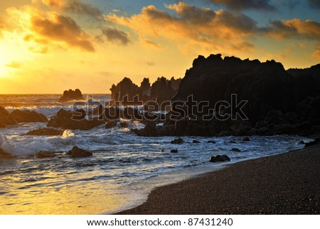 Atlantic sunset over Canary  Island, Lanzarote. Sea wave breaking against coast rock in sunset time