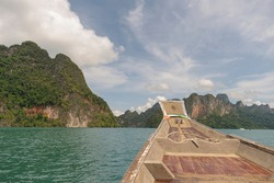 Atmosphere on a tourist boat That overlooks high rocky mountains and dark green water Inside a large dam that is popular with tourists is called Ratchaprapha Dam. Surat Thani Province, Thailand