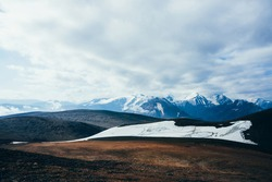 Atmospheric alpine landscape to rocky mountain with glacier. Snowy rockies in highland valley and giant glacial ridge. Snowy mountain range. Flying over mountains. Wonderful scenery on high altitude.