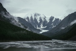 Atmospheric alpine landscape with mountain streams from snowy mountains in overcast weather. Bleak monochrome scenery with glacier tongue in mountain valley in rainy weather. Glacier among low clouds.