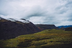 Atmospheric alpine scenery with great snowy mountains and rocks under gray sky. Awesome view to giant mountains with snow on tops in cloudy weather. Dramatic beautiful landscape of highland nature.