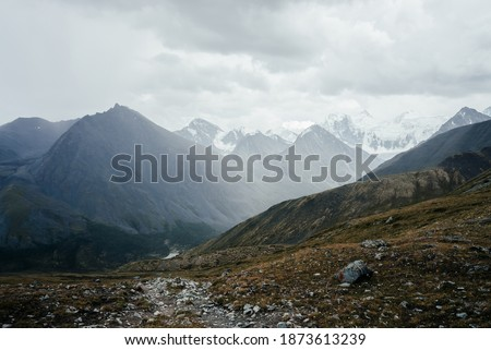 Atmospheric alpine view from pass to great mountain with sharp pinnacle under gloomy cloudy sky. Wonderful giant pointy rocky top and snowy mountains behind mountain pass. Awesome beauty of highlands. Photo stock ©