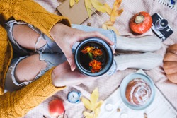 atmospheric autumn background. girl holds cup of coffee. bun, pumpkin, apples, book, headphones, retro camera in frame