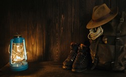 Atmospheric hiking survival style vintage accessories including packed backpack, gas lamp and oldschool boots in the evening inside of remote cabin. Dark background empty space, room for text.