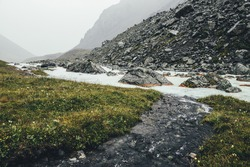 Atmospheric landscape with clear water stream flows into mountain river among moraines in rainy weather. Bleak scenery with milky river among rocks. Clear water stream flows into milk mountain river.