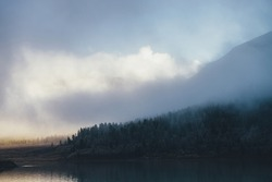 Atmospheric landscape with coniferous trees in hoarfrost on hillside in shadow in thick low clouds near mountain lake with reflected sunlight. Dark forest with frost on hill in dense fog in low light.