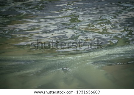 Atmospheric landscape with many channels near shallow lake. Minimal backdrop of dark green water in shoal of mountain lake. Gloomy nature background of deep green water surface and many water streams. Photo stock ©