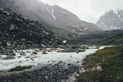 Atmospheric landscape with mountain creek among moraines in rainy weather. Bleak scenery with milky river from snowy mountains. Stones with moss and lichen in water stream. Mountain river among rocks.