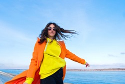Atmospheric lifestyle photo Millennial Hipster Girl in trendy colorful casual outfit. Happy brunette young woman in good mood walks outside on pier next to sea.