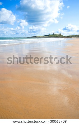 Atmospheric low and wide angle shot of tidal rivulets on Embleton beach with Dunstanburgh castle in the background