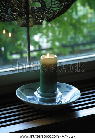 Atmospheric low-light shot of lit candle in the window at dusk with reflections of the flame in the window glass.