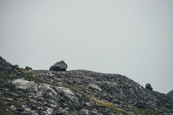 Atmospheric minimalist mountain landscape with rocky hill top with big stones under gray sky. Bleak minimal highland scenery with rocky hill with big stones on top in overcast weather. Gray mountain.