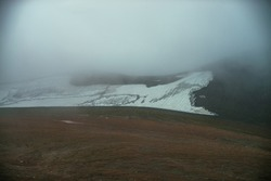 Atmospheric minimalist mountain landscape with small glacier on rocky hill slope inside low cloud. Mountainside with small glacier in dense fog. High mountain valley in low cloud. Poor visibility.