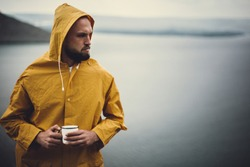 Atmospheric moment. Hipster traveler in yellow raincoat holding metal mug and standing on cliff in rainy windy day with view on lake. Wanderlust. Brutal bearded man hiking. Space