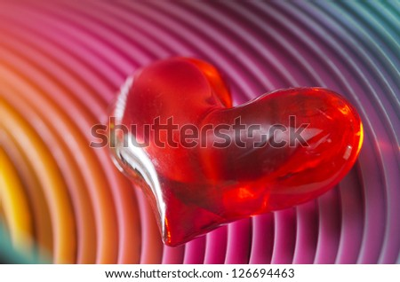 Atmospheric moody image of a glowing red Valentines heart in darkness with a spiralled tube effect background for a dramatic Valentines Day greeting card