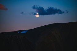 Atmospheric moon landscape of twilight in mountains. Dark lilac sky and big moon with cloud above silhouettes of mountains in dusk. Snow on rocks in moonlight. Purple mountain silhouette with glacier.