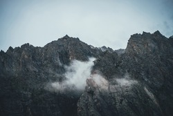 Atmospheric mountain landscape with low clouds on sharp rocks. Awesome rocky mountain with pointy top. Dark rocks in cloudy sky. Beautiful scenery with low clouds on rough crags. Pointed pinnacle.