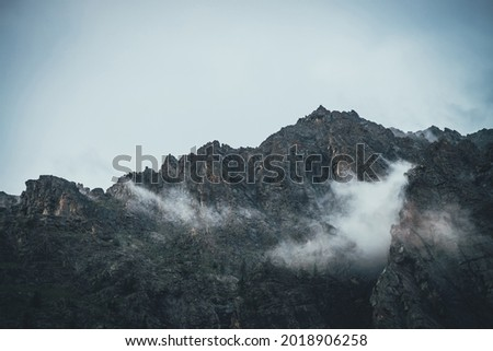 Atmospheric mountain landscape with low clouds on sharp rocks. Awesome rocky mountain with pointy top. Dark rocks in cloudy sky. Beautiful scenery with low clouds on rough crags. Pointed pinnacle. Photo stock ©