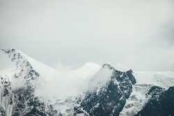 Atmospheric mountains landscape with big snowy mountain top with snow cornices in low clouds. Awesome minimal scenery with snow-white high pinnacle in overcast weather. Giant mountain wall in clouds.