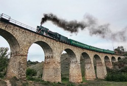 Atmospheric Old steam train on ancient stone railway bridge. Black steam engine with green coaches passes through beautiful stone bridge in valley near Carpathian mountains